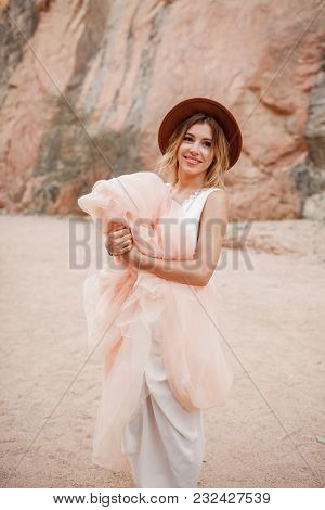 Smiling Bride In Hat Stands And Holds Hem Of Her Long Dress In Canyon On Background Of Rocks And San