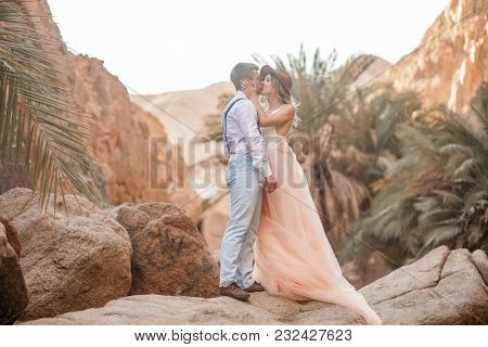 Bride In Long Dress And Groom In Sunglasses Stand And Kiss In Canyon Against Background Of Rocks And