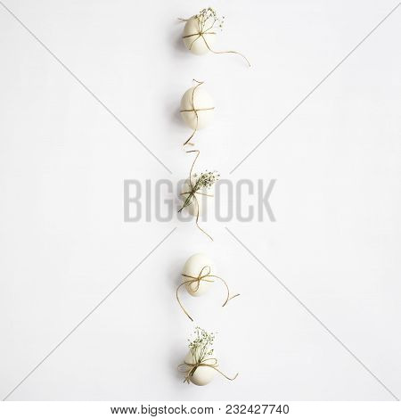 White minimalistic Easter eggs decorated with twine and flowers of gypsophila on a white background