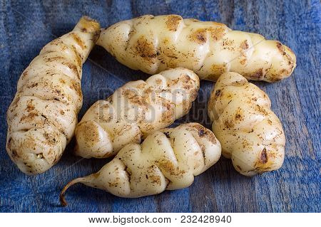 Oxalis Tuberosa Also Known As Oca Tuber On Rustic Background