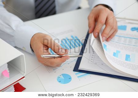 Male Hands Hold Documents With Financial Statistics At Office Workspace Closeup. White Collar Check