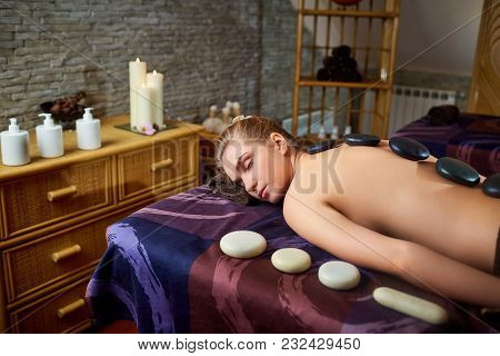Stone Massage Back Spa For A Woman In The Beauty Center.
