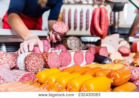 Butcher shop woman holding meat and sausage in her hand
