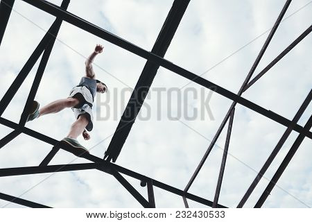 Brave And Risky Man Balancing On The Top Of High Metal Construction, Outdoors