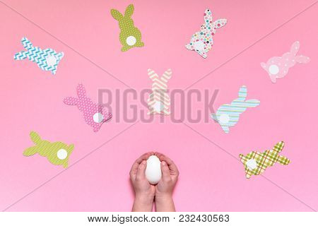 Child Holding In Hands White Egg On Pink Background With Easter Bunny Decorations, Copy Space. Diy H