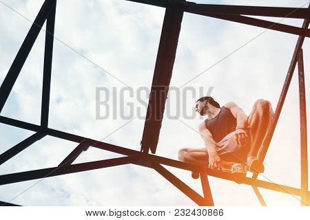 Young Risky Guy Balancing And Sitting On High Metal Construction, Outdoors
