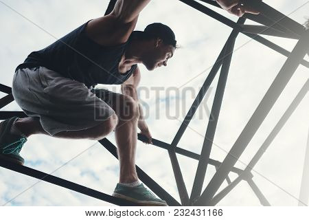 Brave And Risky Man Sitting On The Top Of High Metal Construction, Outdoors