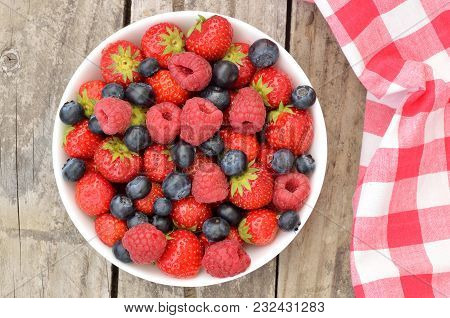 Bowl With Wild Berries - Blueberries, Strawberries, Raspberries On A Wooden Table And A Red Checkere