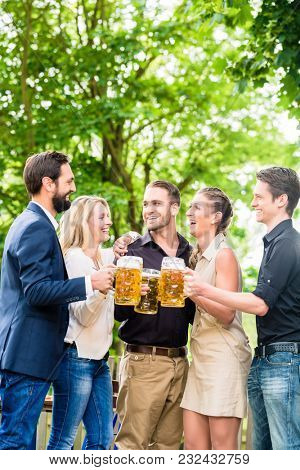 Friends or colleagues on beer garden after work toasting with drinks
