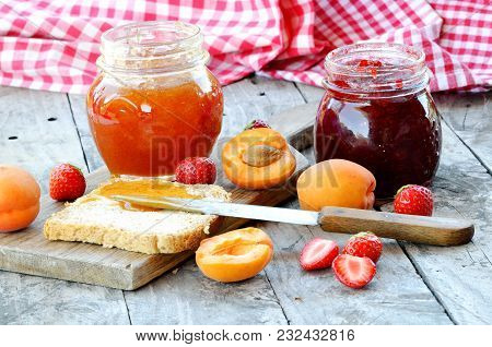 Jar Of Apricot And Strawberry Jam, Fresh Apricots And Strawberries, Knife And Toast Bread With Butte