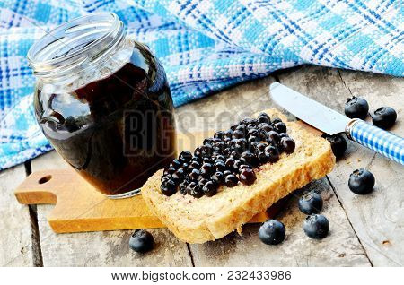 Jar Of Blueberry Jam, Fresh Wild Blueberries, Toast Bread And Knife On Wooden Tables. Blue Dish Clot