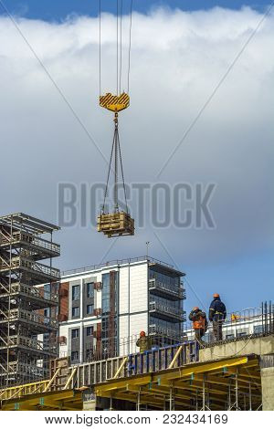 Workers Watching The Load On The Hook Of A Construction Crane
