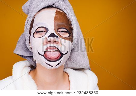 Funny Young Girl With A Towel On Her Head Showing Tongue, On Face Mask With Dog Face