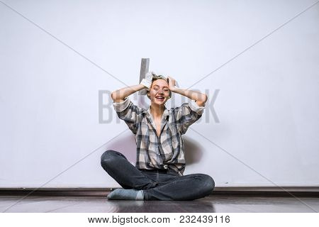 Happy Young Girl Sits On The Floor In Her Apartment, Rejoices That She Has Made Repairs