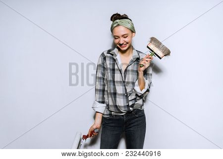 Laughing Young Girl Doing Repairs In Her Apartment, Holding Brush And Roller In Hands