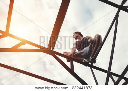 Risky Brave Man Balancing And Sitting On High Metal Construction, Outdoors