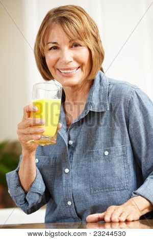 Mid age woman drinking orange juice