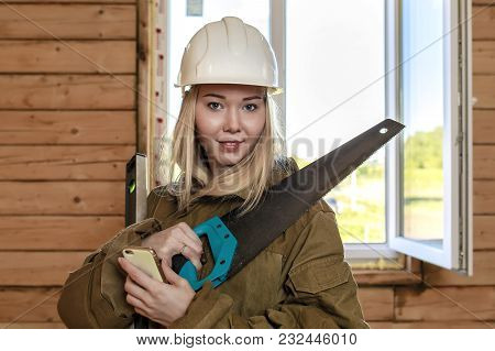 Young Naughty Blonde Girl Builder In A White Helmet With A Saw, A Level And A Cell Phone At The Cons