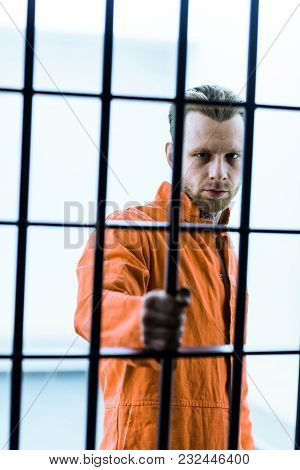 Prisoner Holding Prison Bars And Looking At Camera