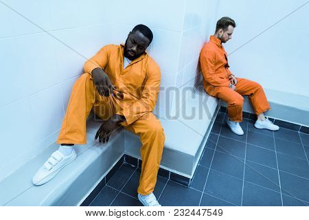 High Angle View Of Multicultural Prisoners Sitting On Benches In Prison Cell
