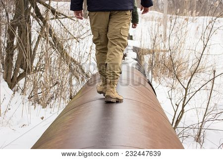Guy Is Walking On A Wide Water Pipe Around Is Lying Snow Walk In The Cold Season