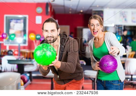 Couple playing Bowling at bowling center