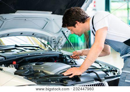 Car mechanic working in car service workshop