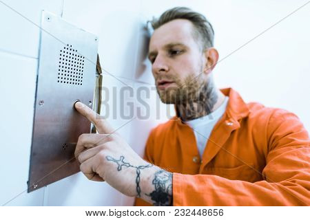 Tattooed Criminal In Orange Uniform Pressing Button In Prison Cell