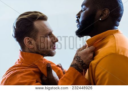 Side View Of Multiethnic Prisoners Threatening Each Other And Holding Collars