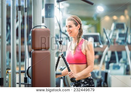 Happy and beautiful fit woman wearing pink fitness bra while exercising cable rope triceps extension at the gym