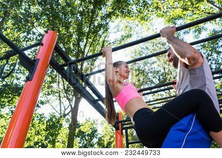 Fit young woman smiling while doing pull-ups supported by her strong partner during couple workout routine in a calisthenics park in summer