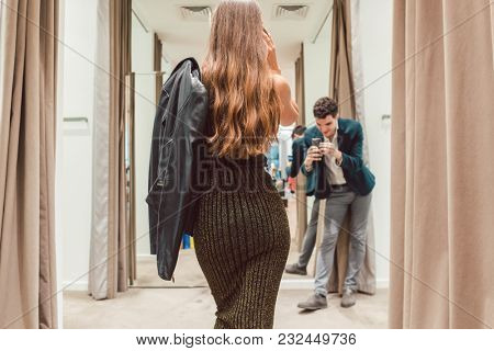 Man making phone photo of his wife with her new dress in fashion store