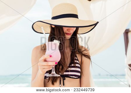 Sexy woman in beach vacation drinking a cocktail in pavilion