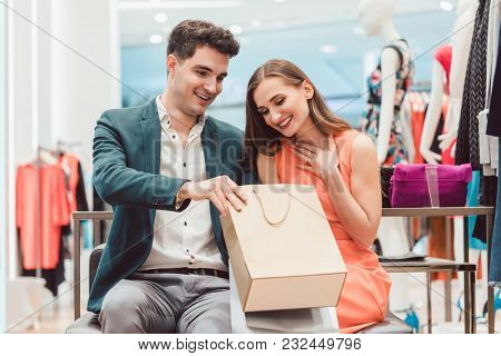 Woman showing her man in shopping bag what she bought in fashion store
