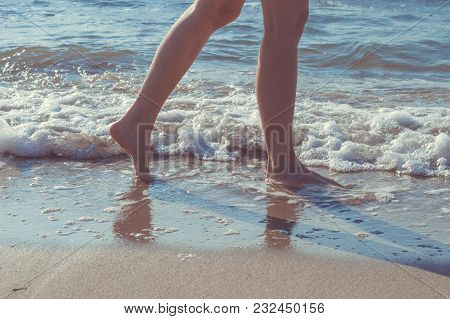 Close Up Of Woman Legs Walking Barefoot On Beach In Summer Holidays. Vacation Concept.