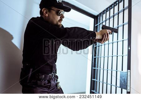 Prison Guard Aiming Gun And Looking Away