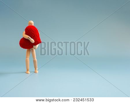 Wooden Puppet Standing And Holding A Red Heart On The Blue Screen Background. Wooden Puppet Holding