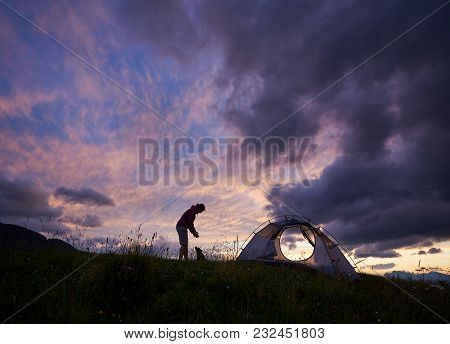 Silhouette Of A Female Traveller Playing With Small Dog Near Her Tent On The Mountain Top During Spe