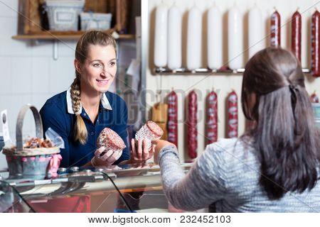Sales lady in butchery shop serving customer selling meat