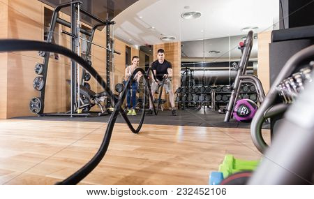 Low-angle view of a young determined man waving battle ropes with alternative motion during an intense session of functional training in the gym