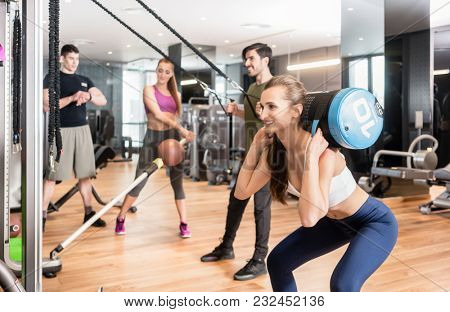 Young determined fit woman doing squats exercise, while holding on the back of her neck a heavy sandbag during group circuit functional training at the gym