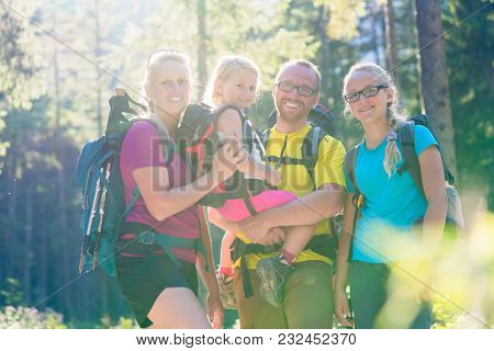 Family with two daughters on hike in the woods backlit in summer