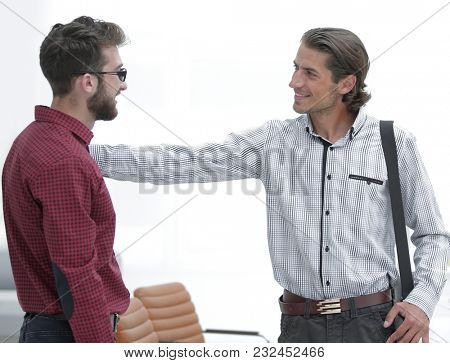 two employees are talking in the office