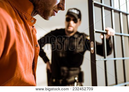 Cropped Image Of Prison Guard Looking At Criminal In Prison Cell