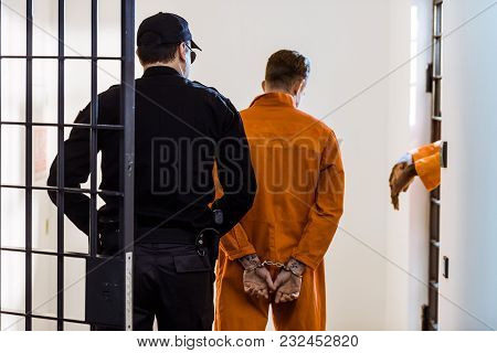 Back View Of Security Guard Leading Criminal In Handcuffs