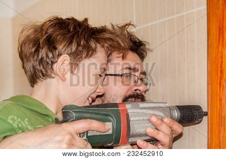 Son With Father Drill A Wall In The Bathroom With A Perforator