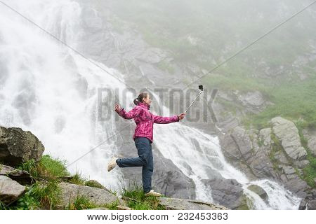 Smiling Young Female Making Selfie Posing On Rock In Front Of Magnificent Balea Waterfall In Romania