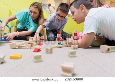 High-angle view of a young female educator teaching children to build with patience a wooden train circuit, during playtime on the floor in the kindergarten classroom