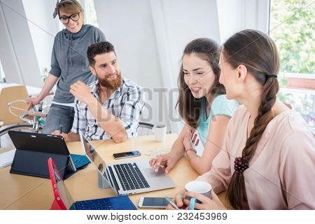 Young proficient co-workers smiling and collaborating while using wireless portable technology for telecommuting in a modern shared office space