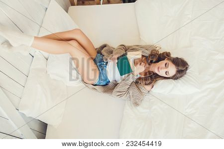 Young Woman Lying On Bed And Relaxing At Home With Book, Casual Style